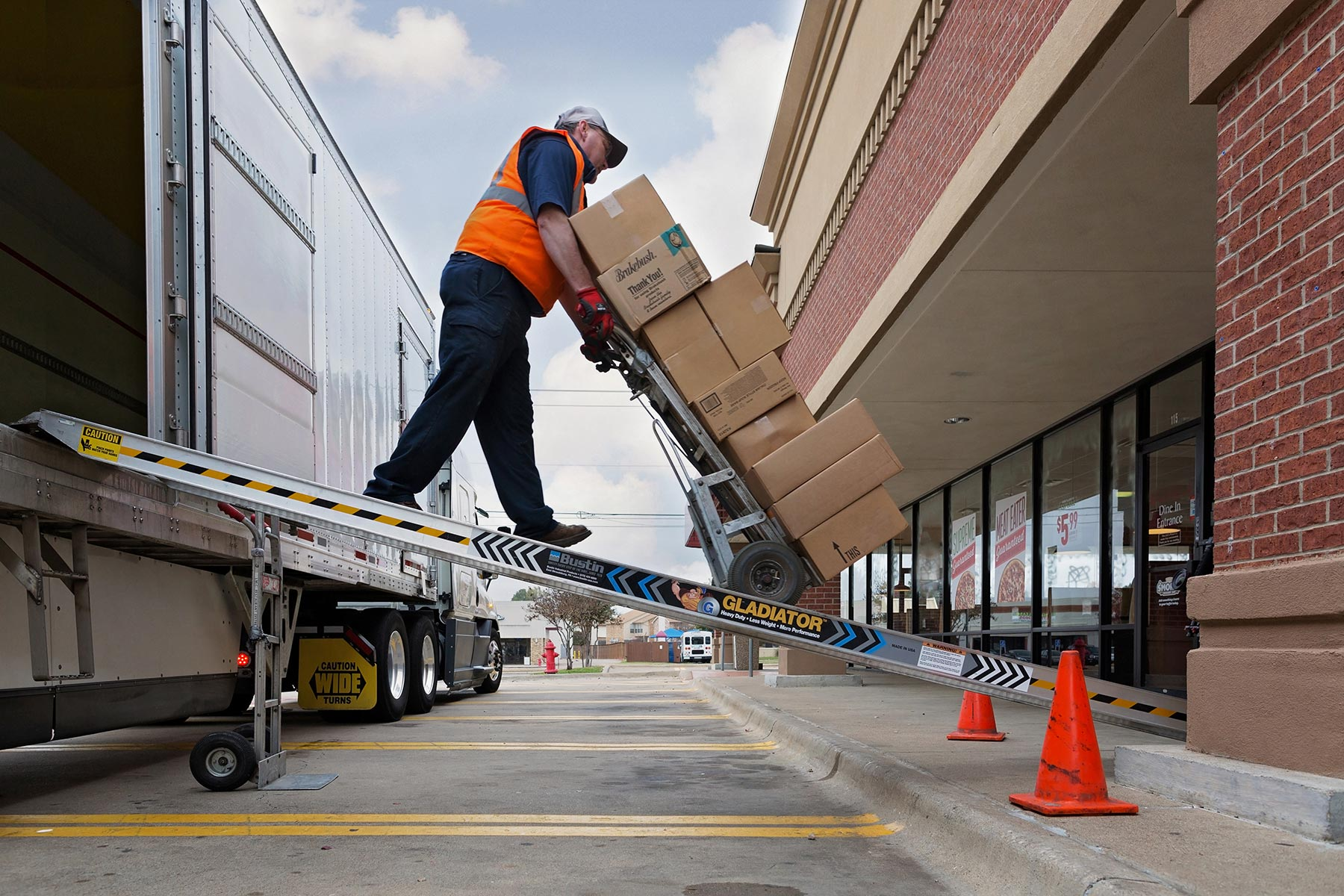 Man with a tall stack of boxes on a hand truck moving down a ramp from a truck